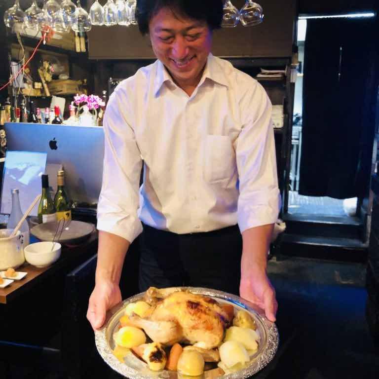 bar7557のスタッフが貸切パーティーの時に笑顔でお料理を説明している写真です。